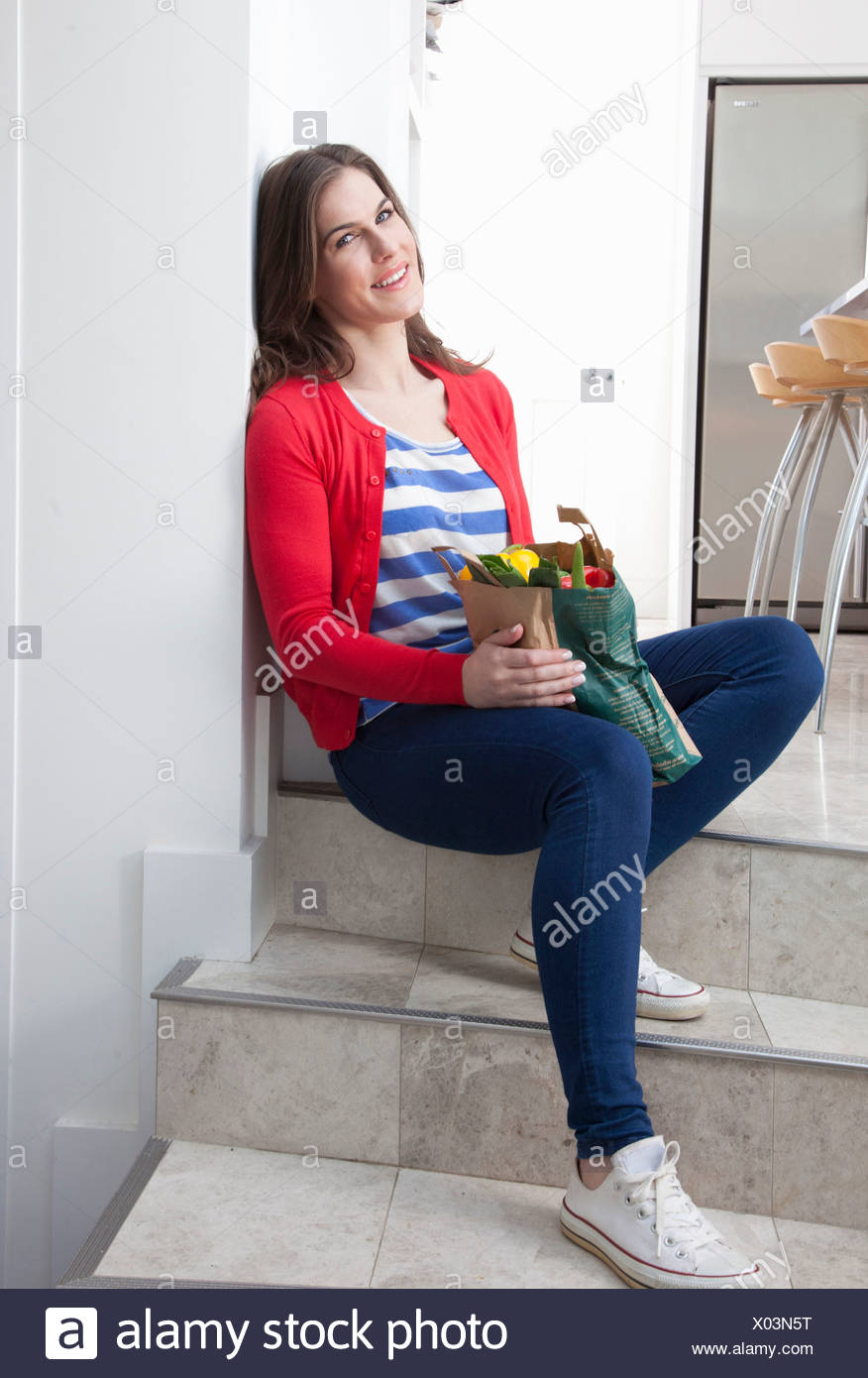 Young woman sitting on kitchen step with grocery bag - Stock Image