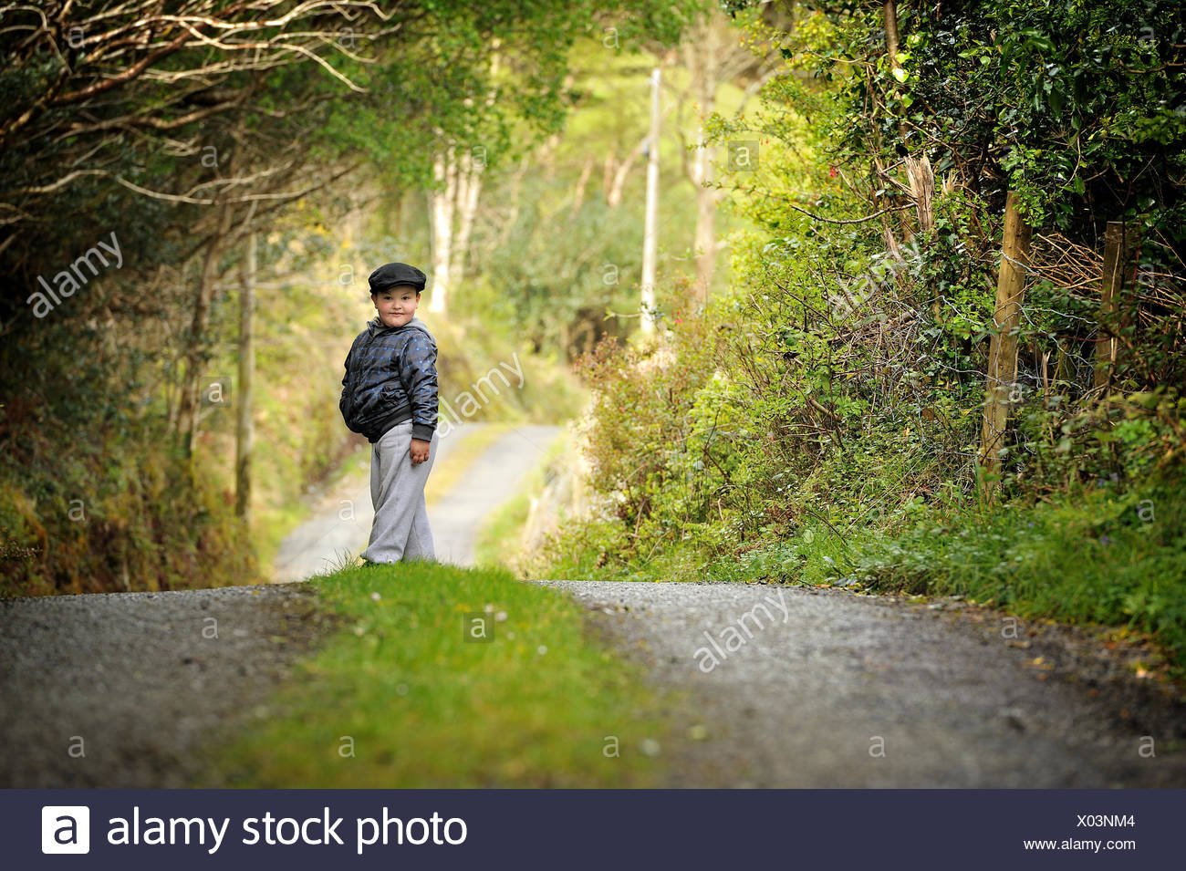 Boy standing in the middle of country road - Stock Image