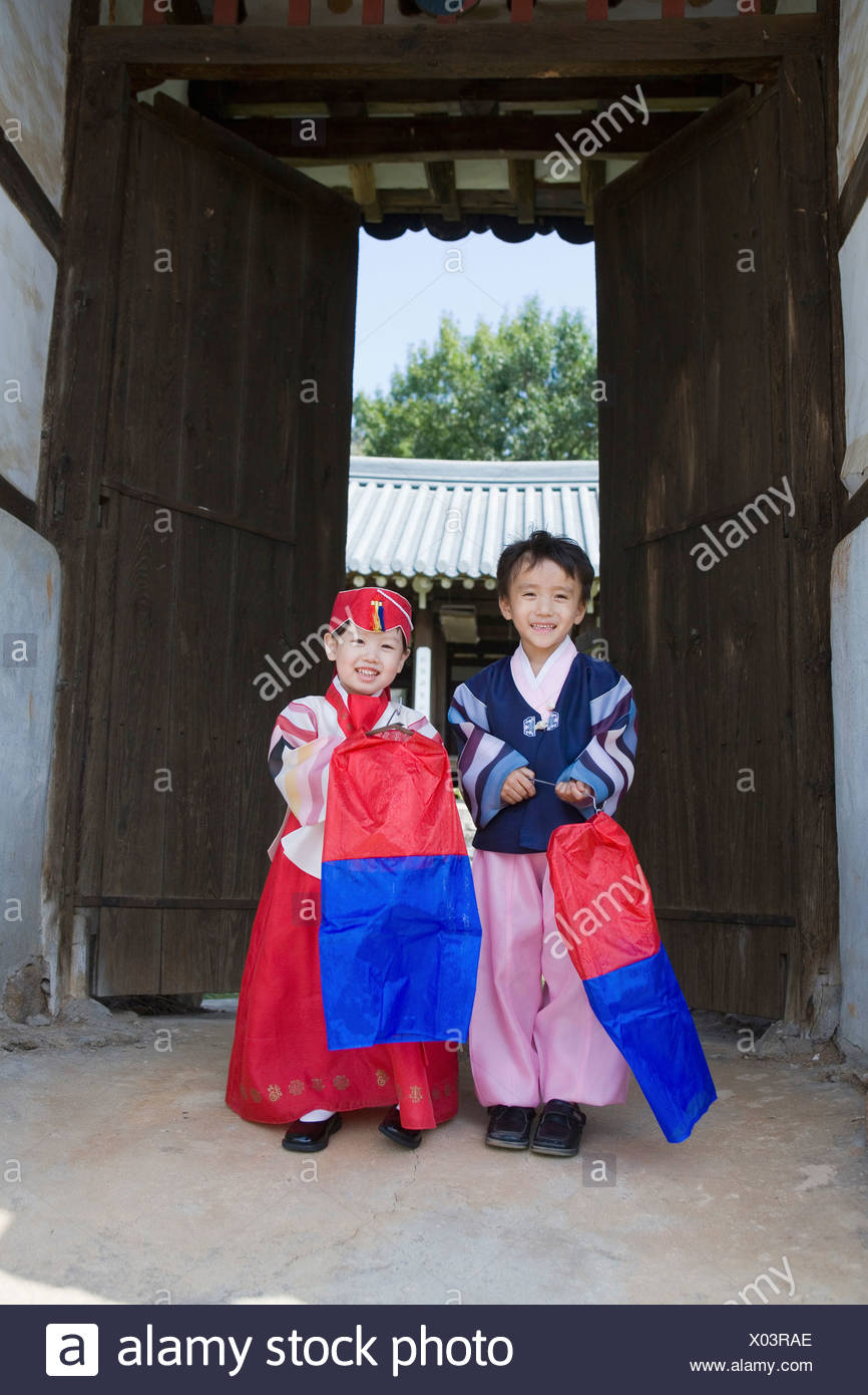 095185b40 boy and girl in Korean traditional costume holding traditional Korean  lantern with a red-and