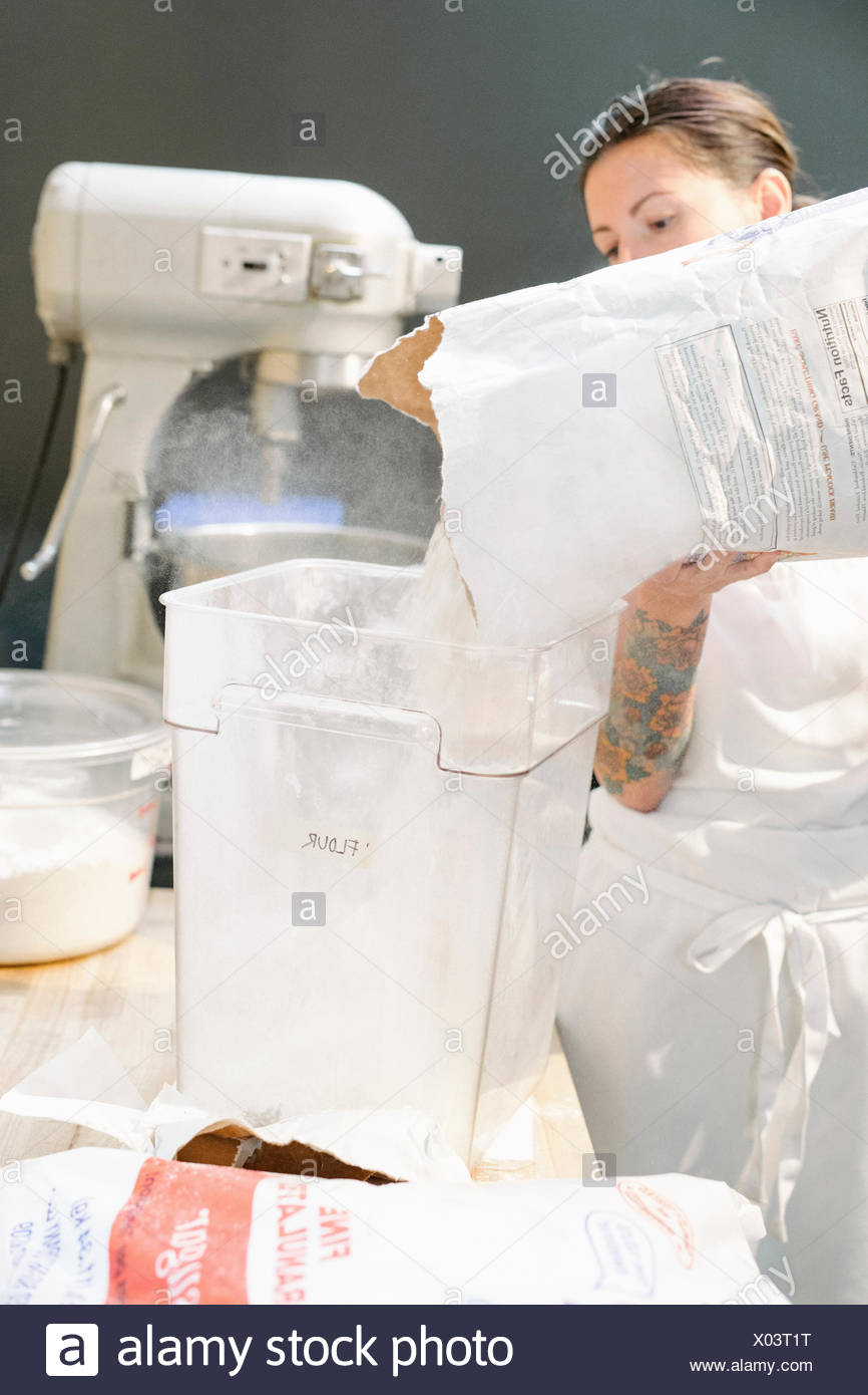 Woman wearing a white apron at a work counter in a bakery, pouring flour into a container. - Stock Image