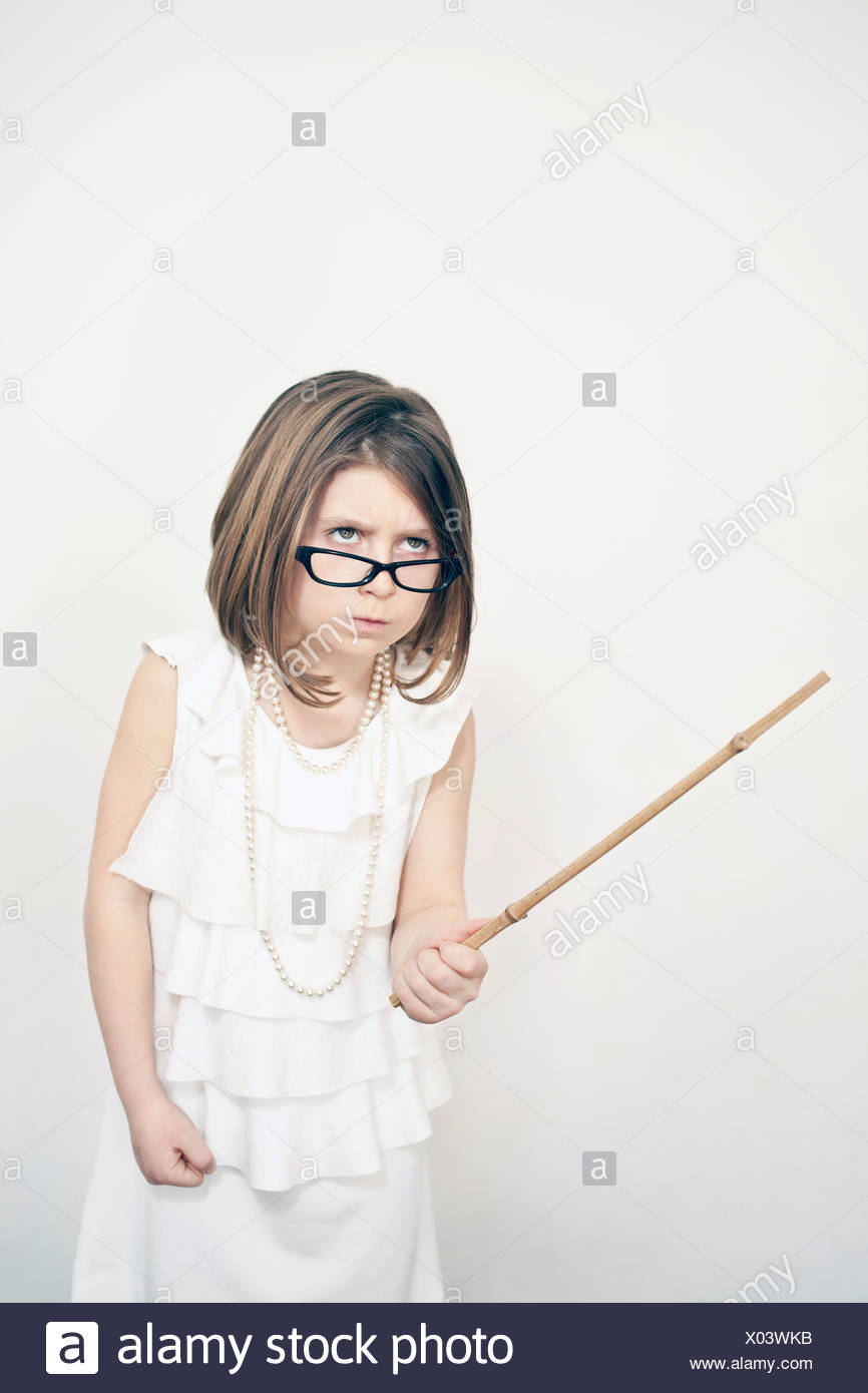 Frowning girl holding stick - Stock Image