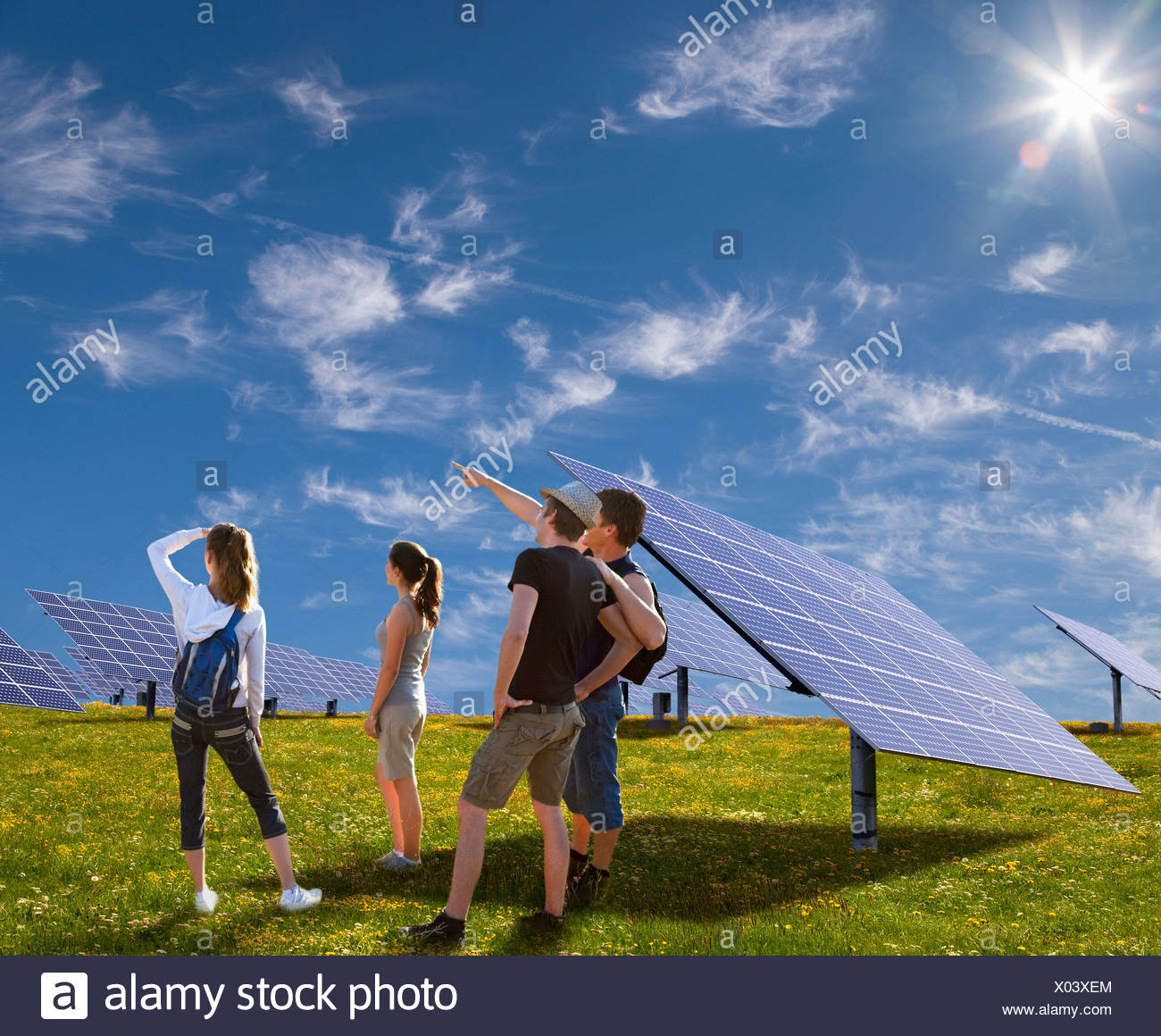 People standing in field by solar panels - Stock Image
