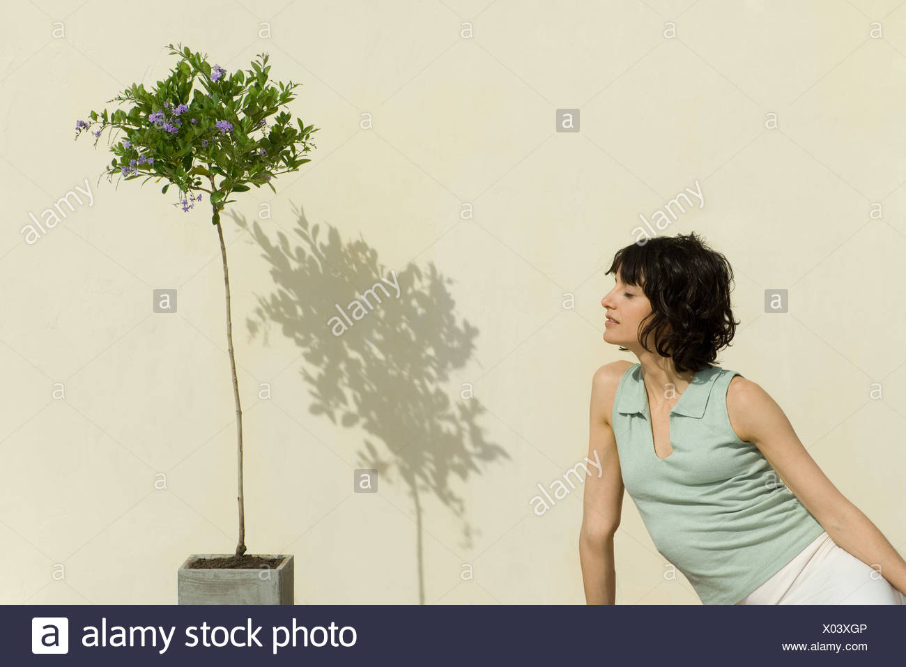 Woman sitting outdoors, leaning toward flowering plant, eyes closed - Stock Image