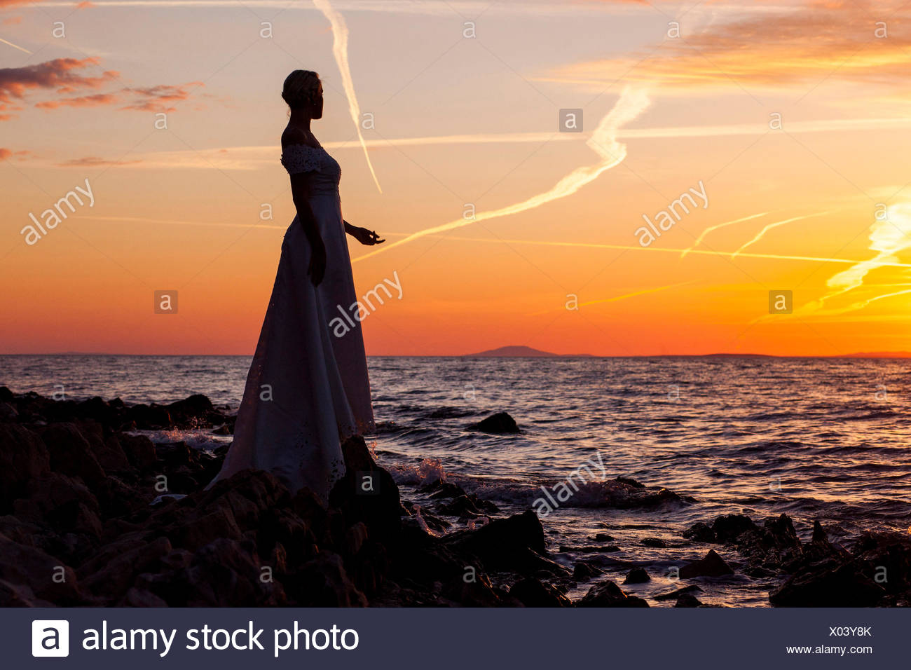 Bride overlooking sea against sunset - Stock Image