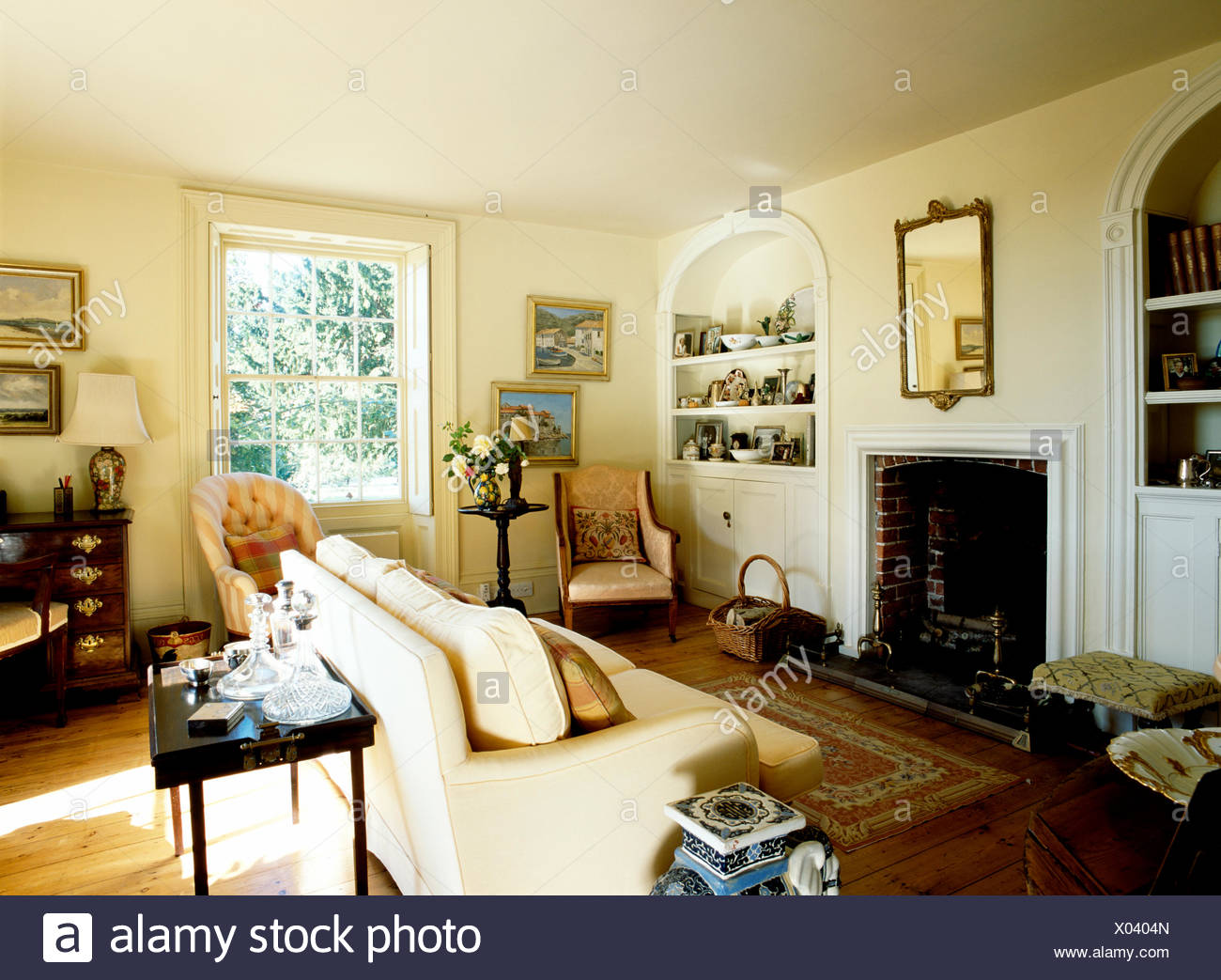 Alcove Shelving On Either Side Of Fireplace In Cream Country Living Room  With Cream Sofa And Antique Chairs