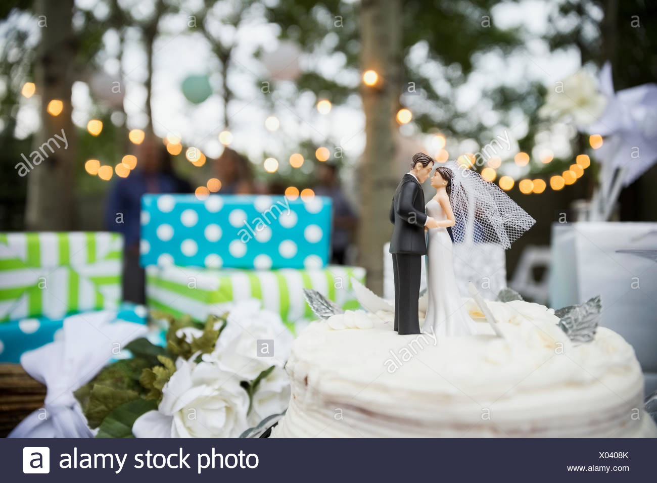 Bride and groom cake topper on cake - Stock Image
