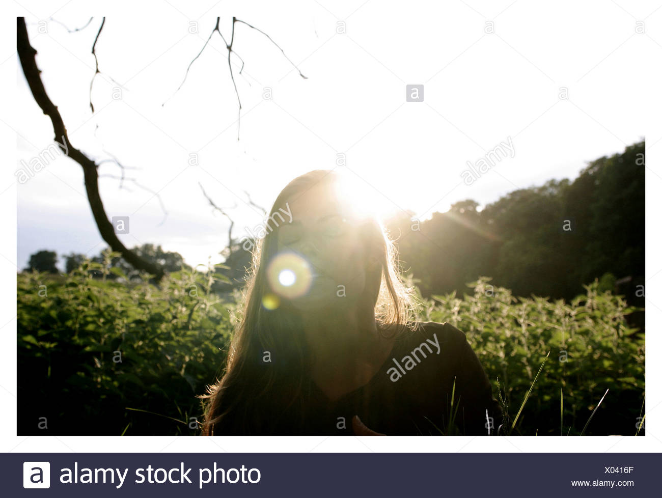 A woman standing with her eyes closed the sun shining in the background - Stock Image