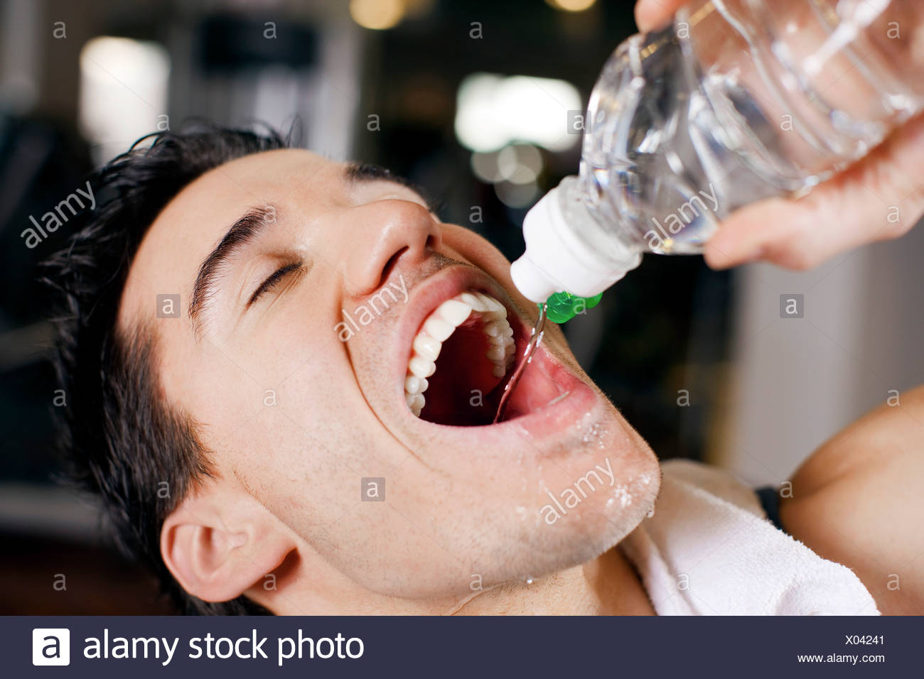 headshot of young man drinking water from bottle in gym Stock Photo
