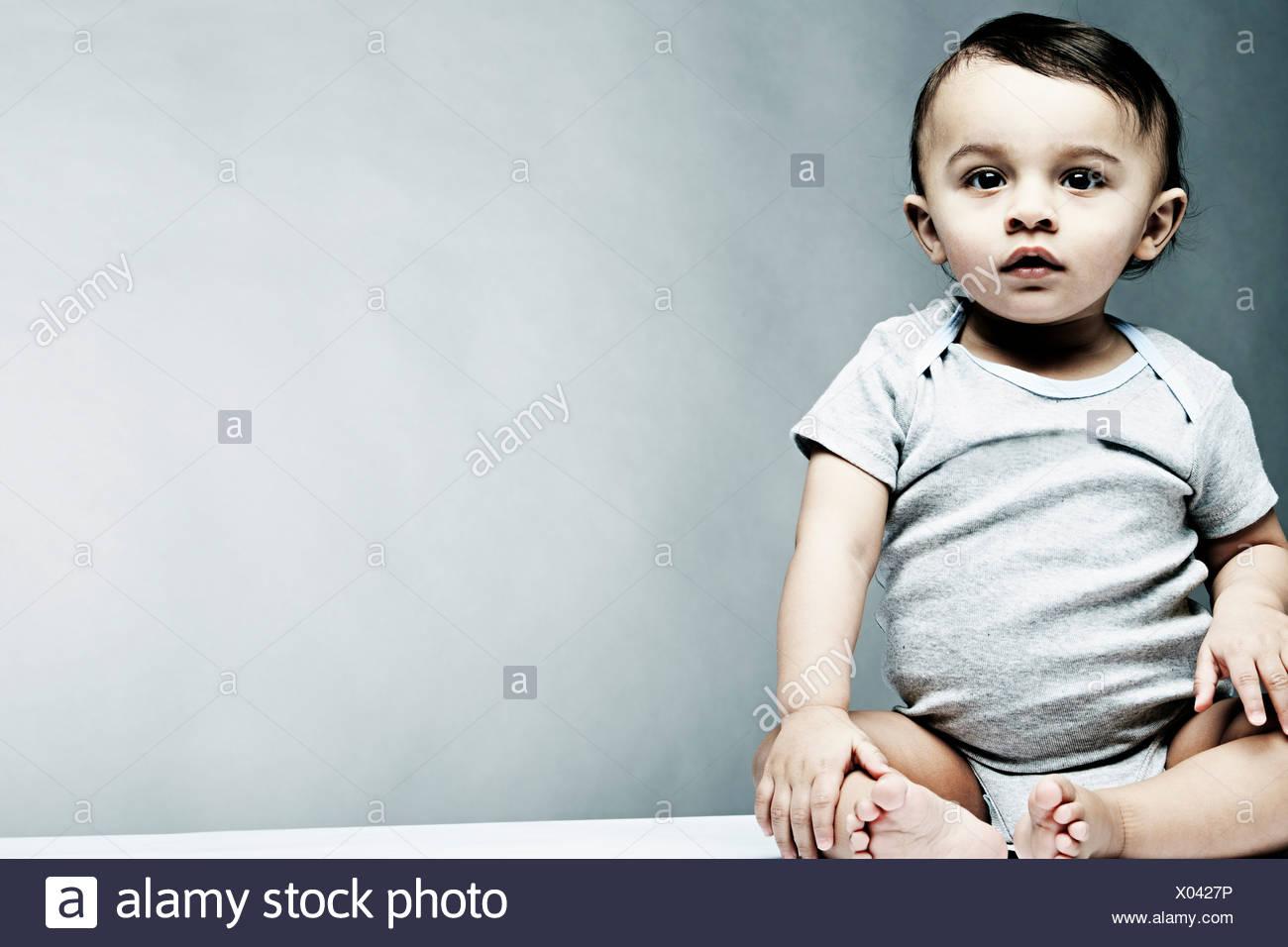 Portrait of baby boy wearing grey baby vest - Stock Image
