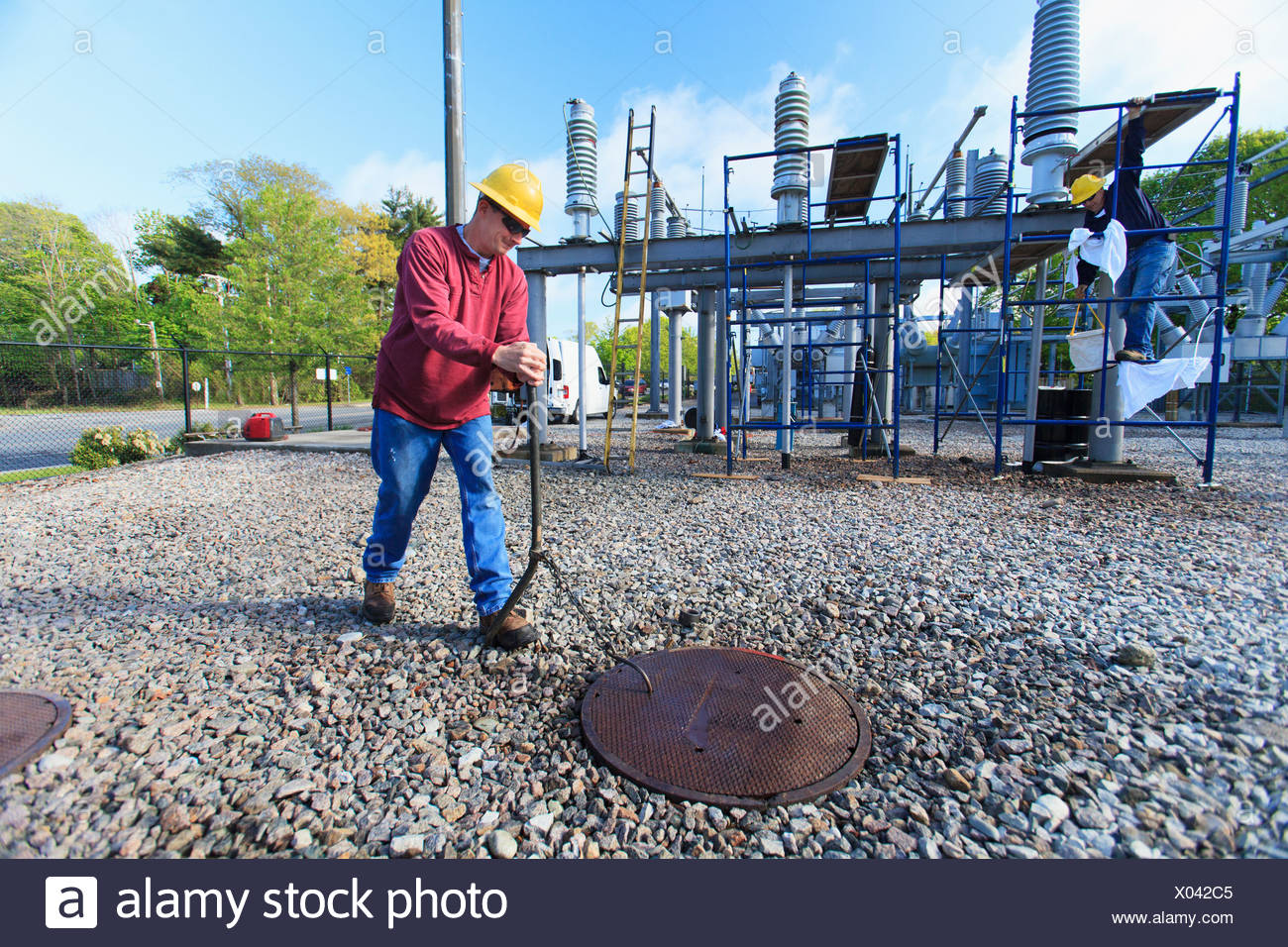 Power engineer accessing manhole cover at high voltage power distribution station - Stock Image
