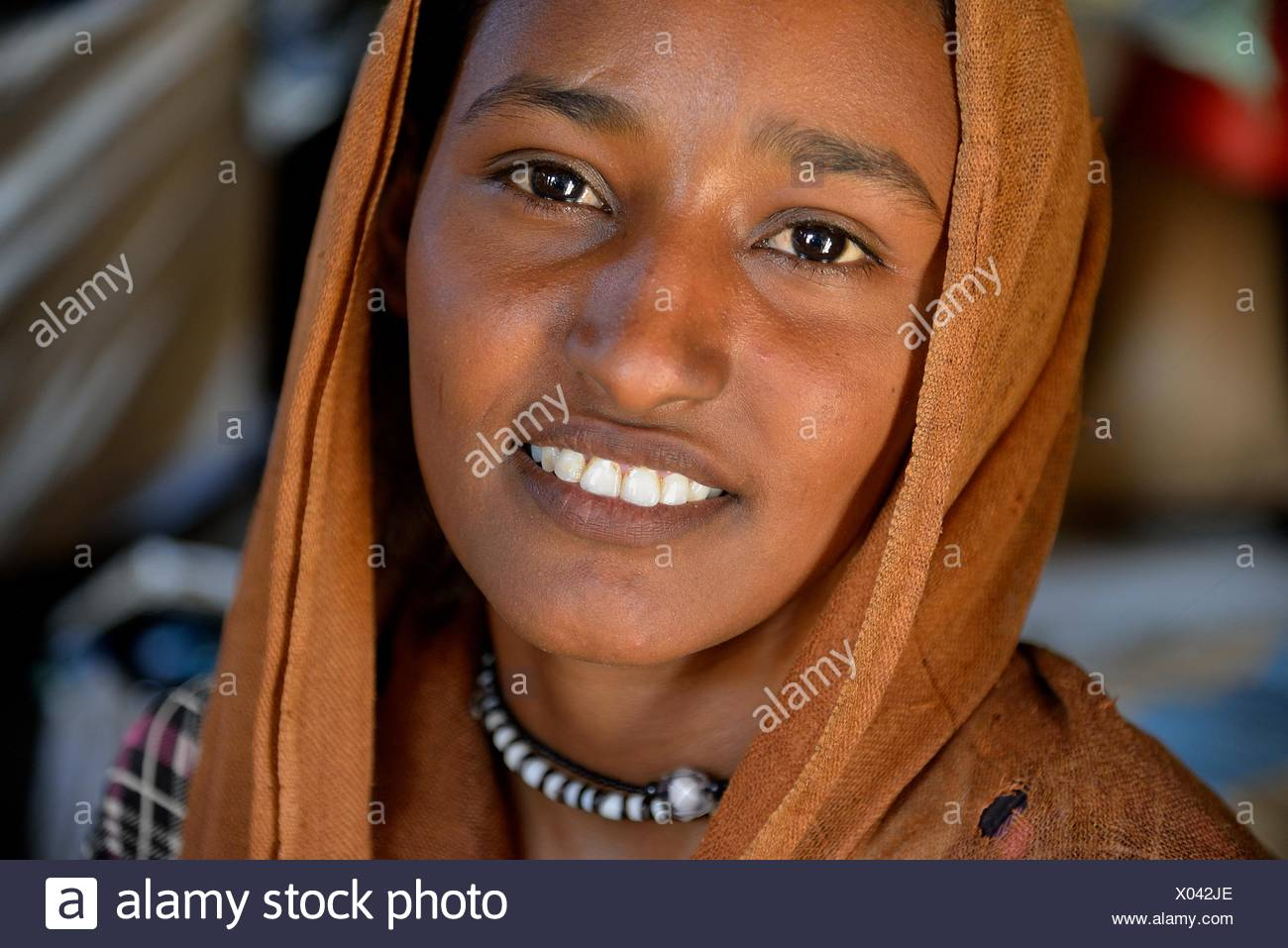 Young girl from the nomadic tribe of the Bush Arian with headgear, Portrait, Bayuda Desert, in Karima, Nubia, Northern Sudan - Stock Image
