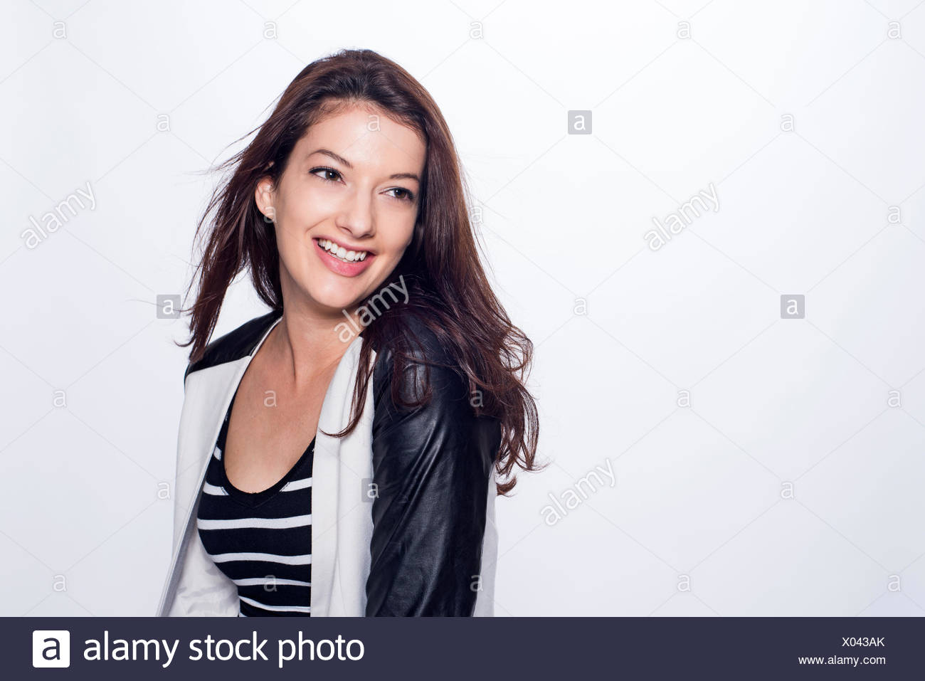 Studio portrait of young woman with long dark hair, smiling - Stock Image
