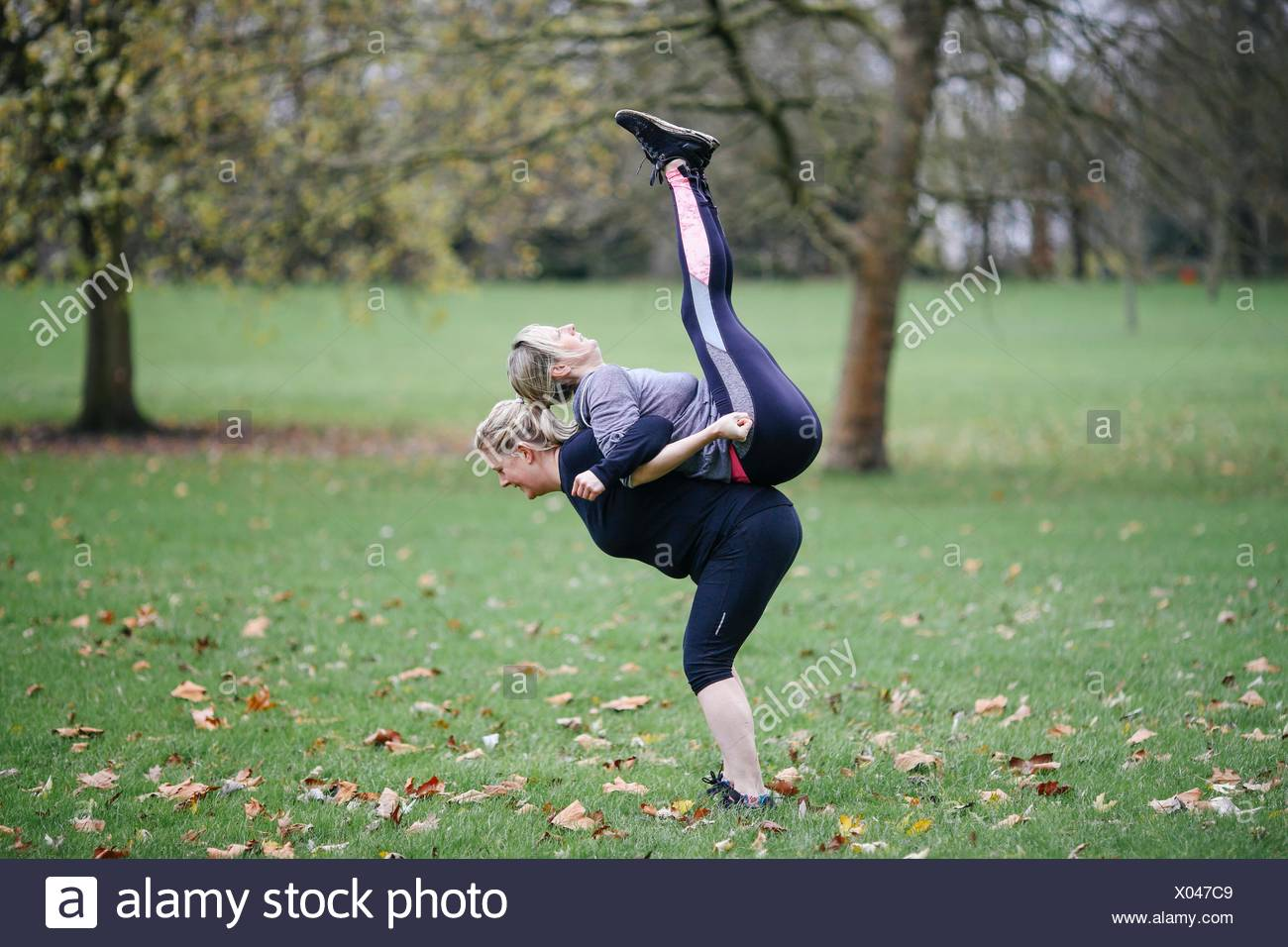 Two women doing back to back exercises in park - Stock Image