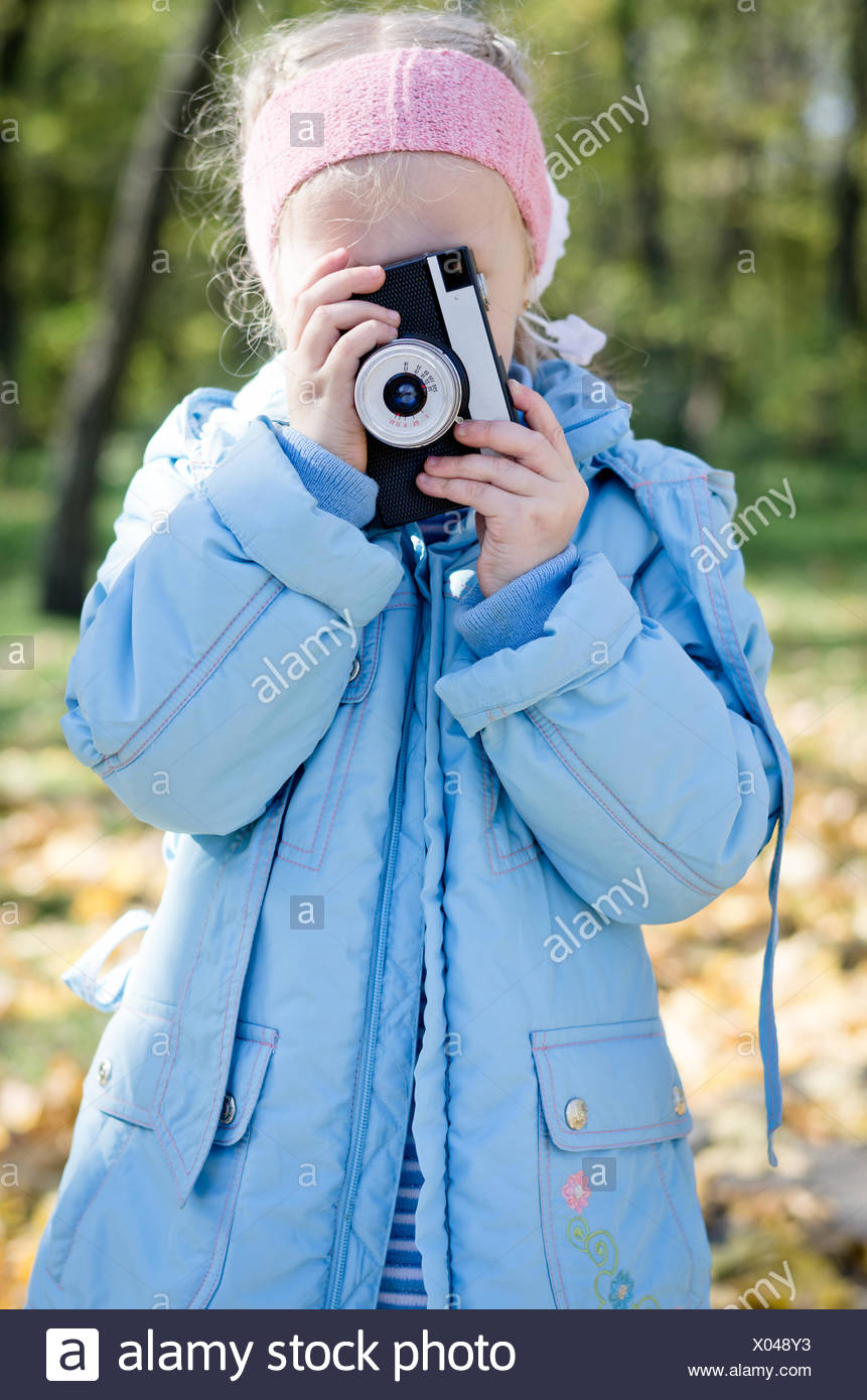 Small girl playing with an slr camera - Stock Image