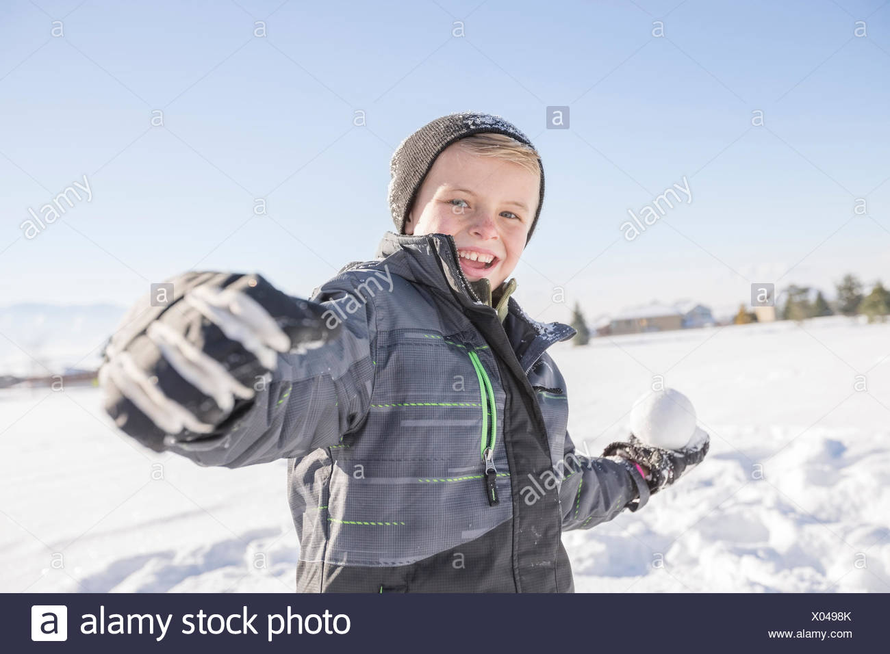 Boy (8-9) throwing snowball - Stock Image