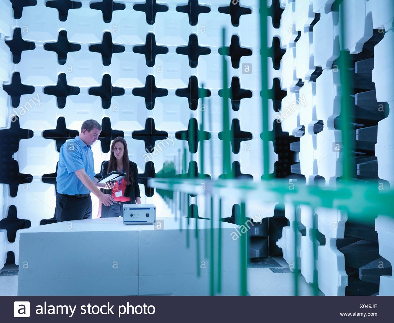 Engineers checking the equipment under test (EUT), in a semi anechoic chamber with energy absorbers and bilog antenna set up for electromagnetic compatibility (EMC) radiated immunity testing - Stock Image