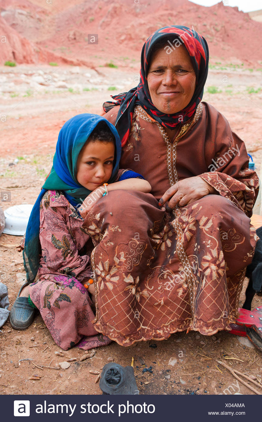 Nomadic cave-dwellers, Berber, a friendly woman and a little girl sitting on the floor, Dades Valley, High Atlas Mountains - Stock Image
