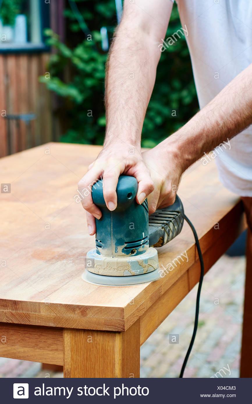 Man sanding an oak table with a random orbital sander - Stock Image