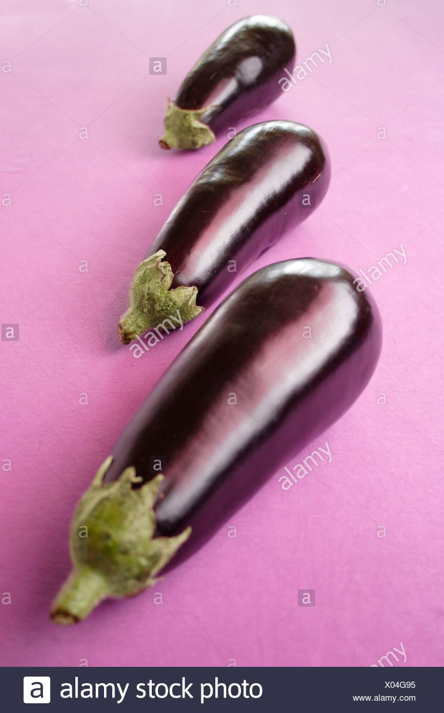 Three aubergines against lilac subsurface Stock Photo