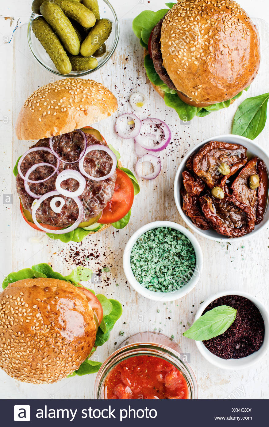 Homemade beef burgers with onion, pickles, fresh vegetables, spices, sun-dried tomatoes and tomato sauce on serving wooden board - Stock Image