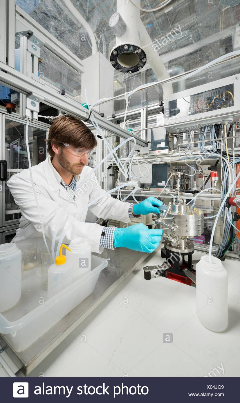 Male scientist, doing research on a innovative technology for mixing chemicals, at a hightech startup company - Stock Image