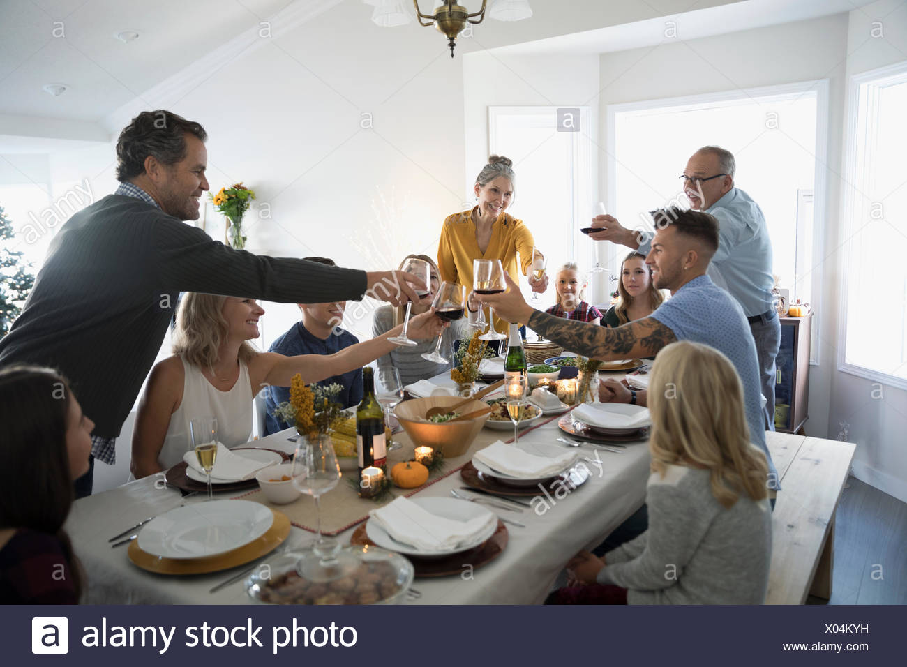 Family and friends toasting champagne and wine glasses at Thanksgiving dinner table - Stock Image
