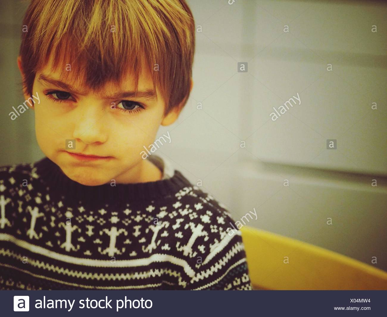 Portrait Of Angry Boy Making Face - Stock Image
