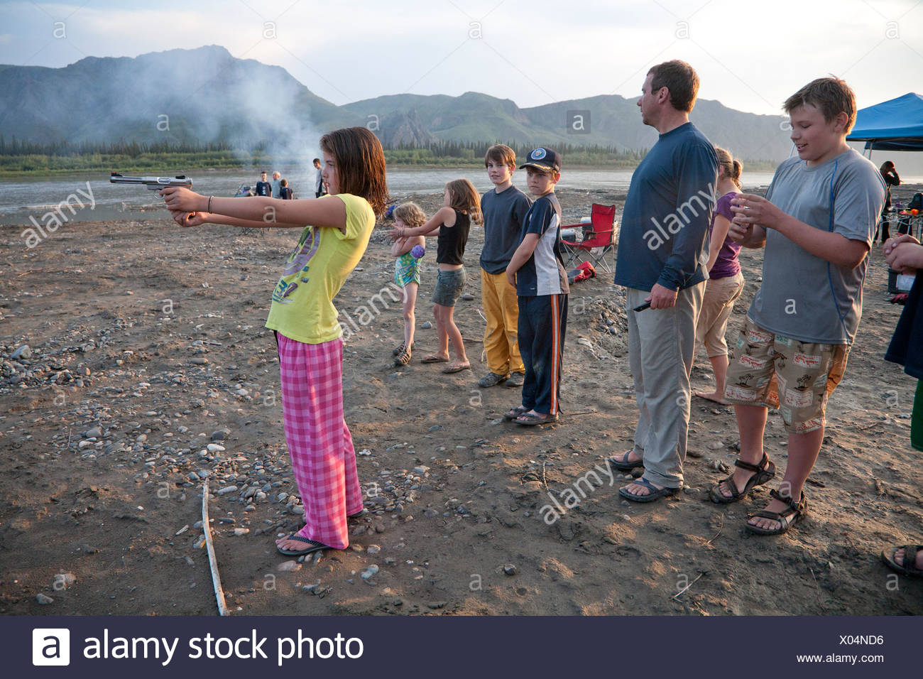 Young girl shoots a pistol in her pajamas and flip-flops at the edge of the Yukon River, Yukon-Charley Rivers National Preserve - Stock Image