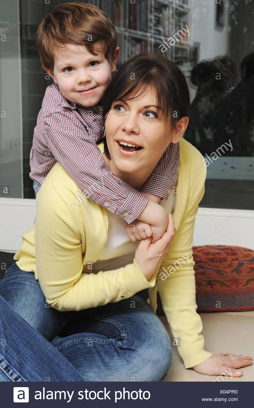Mother playing with son in living room - Stock Image