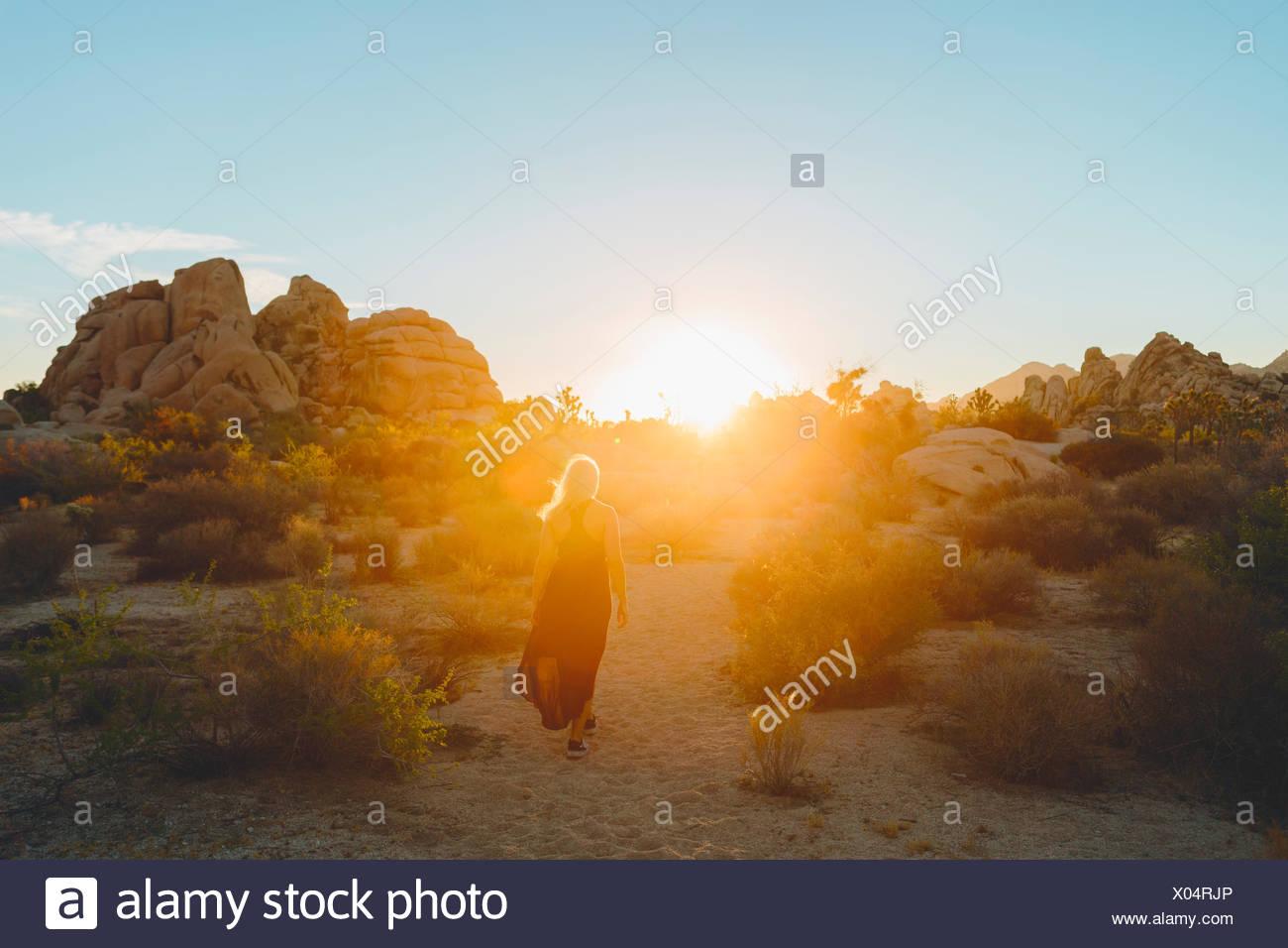 USA, California, Joshua Tree National Park, Woman wearing dress hiking at sunset - Stock Image