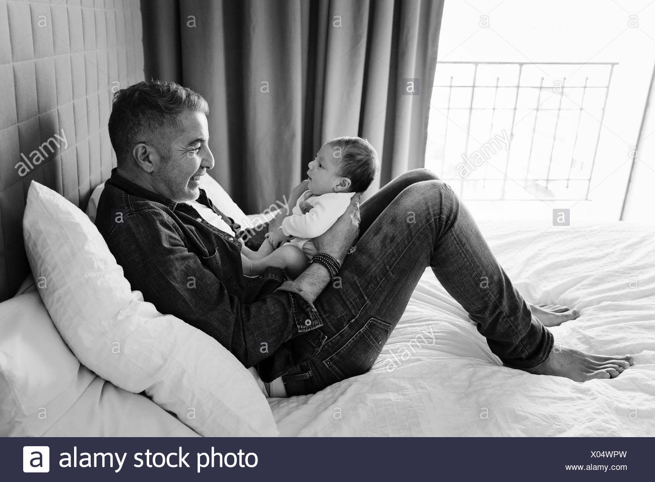 A father and his small baby gazing at each other, side view. - Stock Image