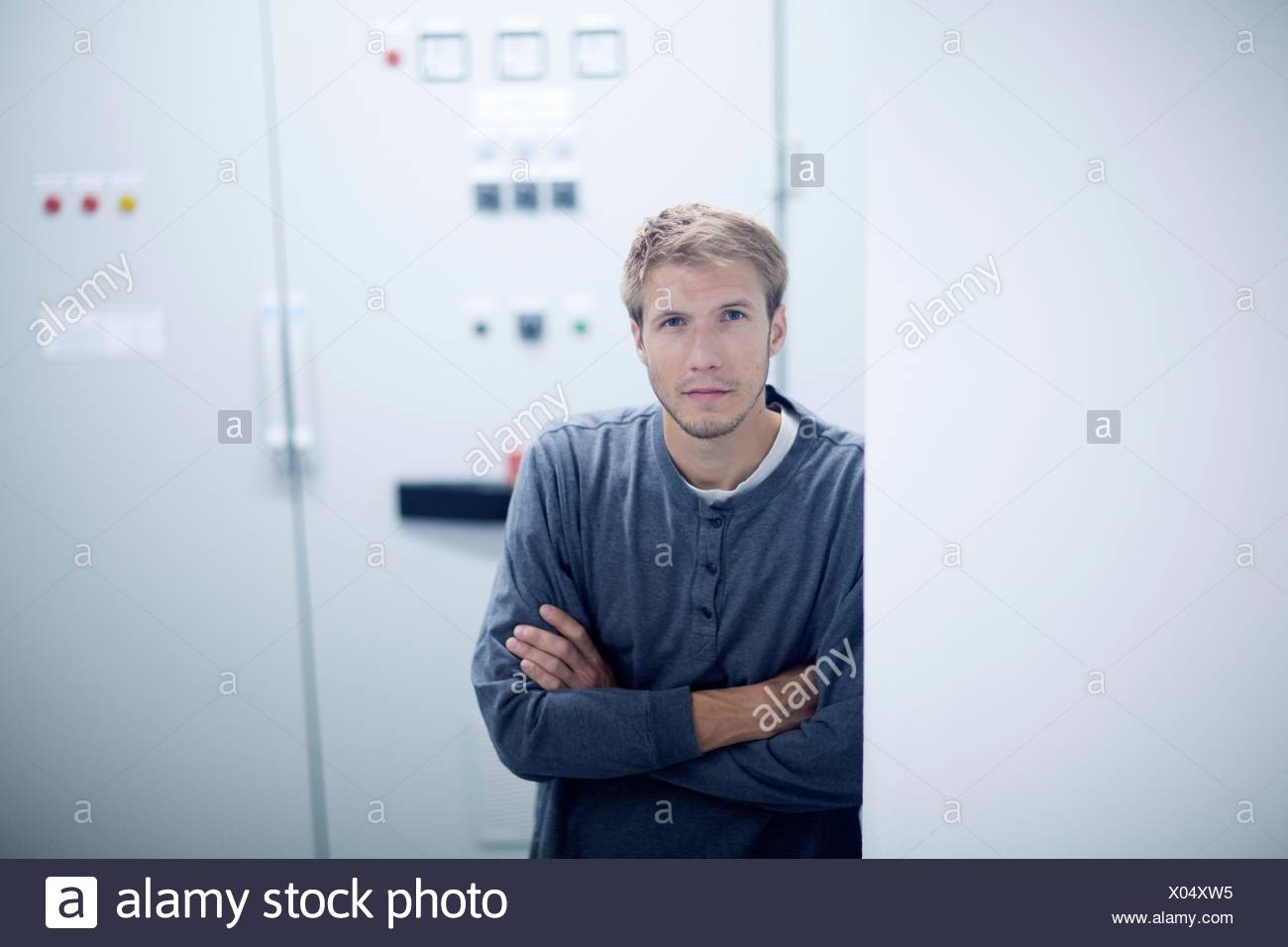 Portrait of young male technician in technical room - Stock Image