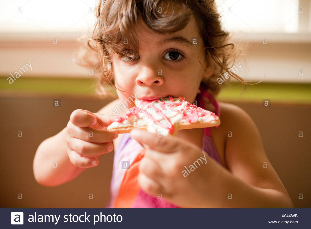 Girl eating star shaped cookie - Stock Image