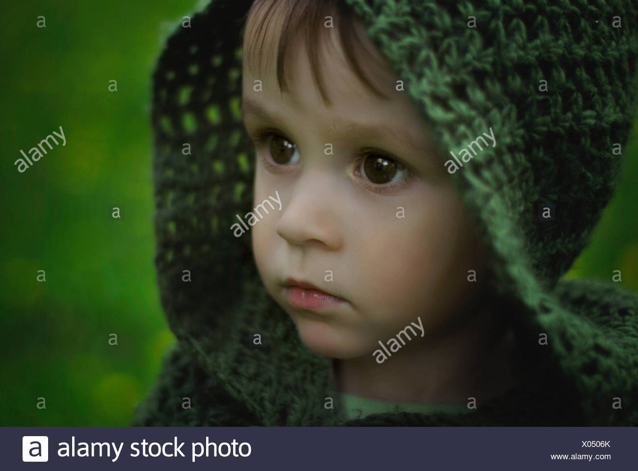 Poland, Portrait of baby boy in green hood - Stock Image