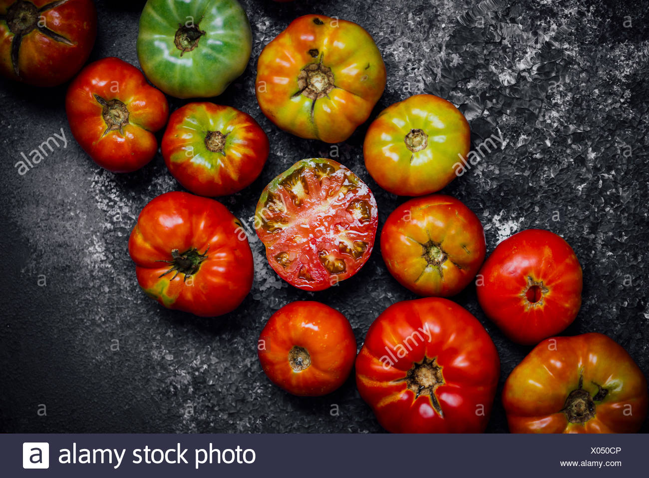 Heirloom Tomatoes gathered on a board and one halved red tomato is in the center. - Stock Image