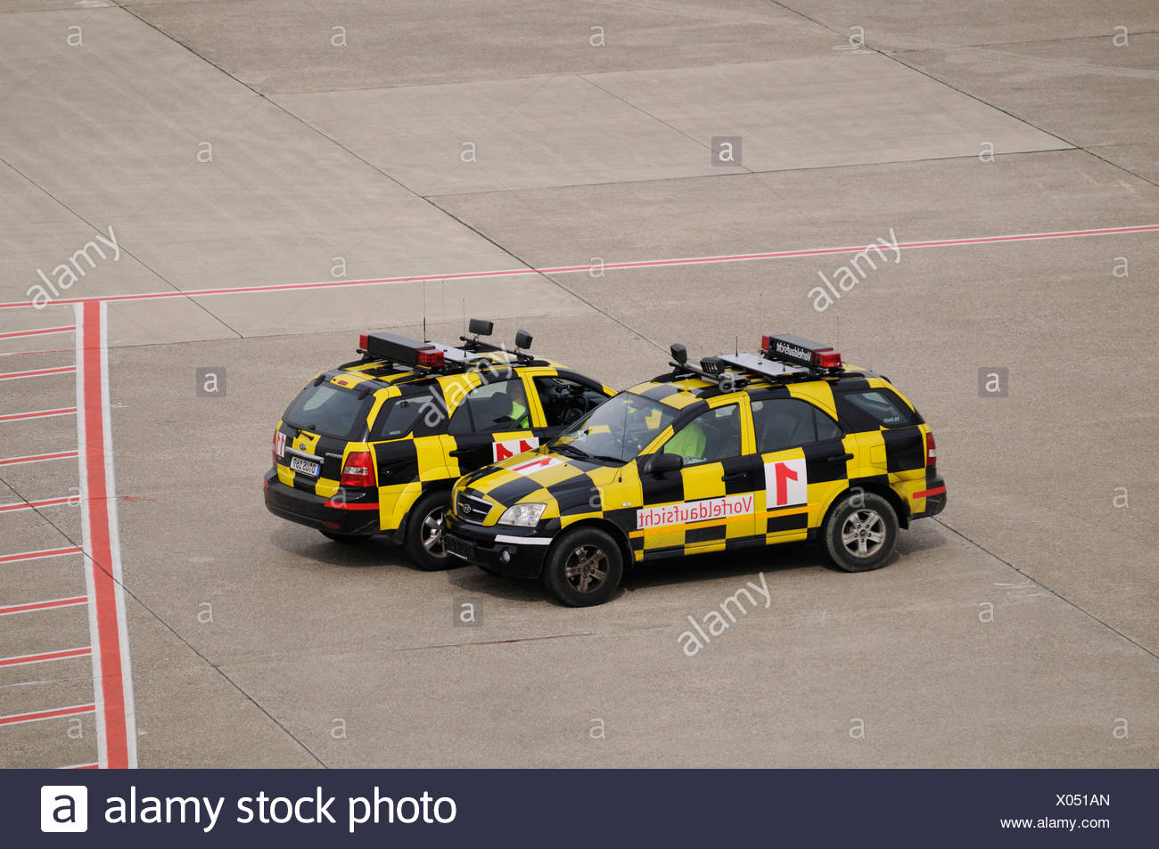 Two yellow and black chequered vehicles on a runway, follow-me cars, Duesseldorf International Airport, North Rhine-Westphalia, - Stock Image