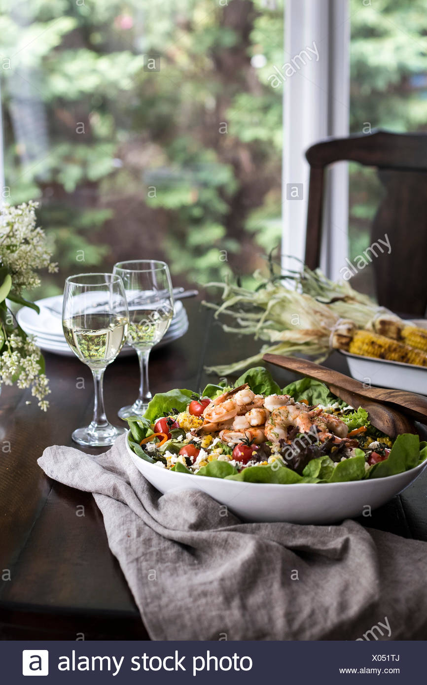 A big bowl of grilled shrimp and corn salad accompanied with two glasses of white wine are photographed from the front view. - Stock Image