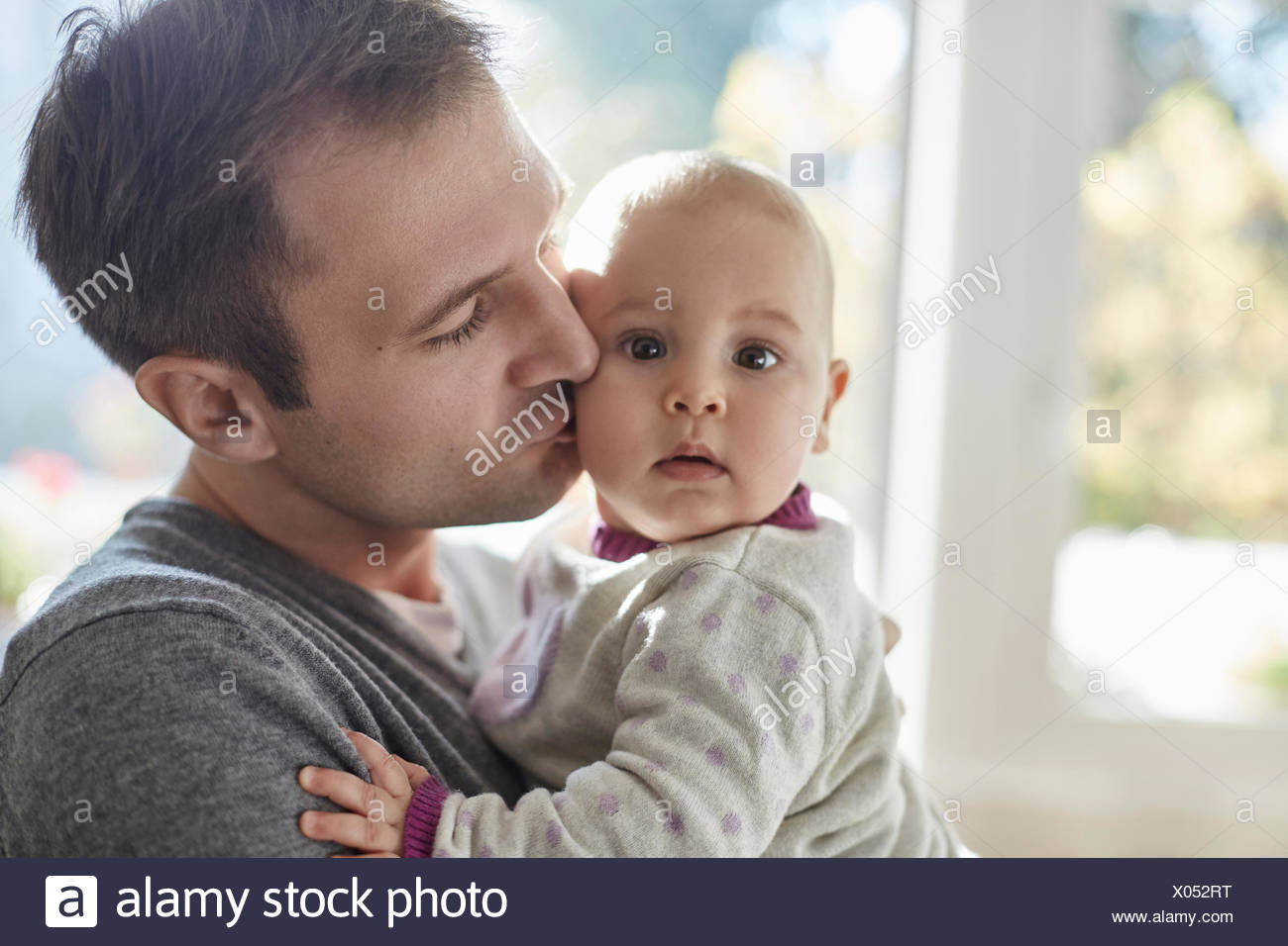 Portrait baby daughter being kisses on cheek by father - Stock Image