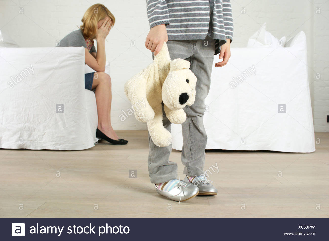 Despaired woman sitting in armchair, girl holding stuffed animal standing in foreground - Stock Image