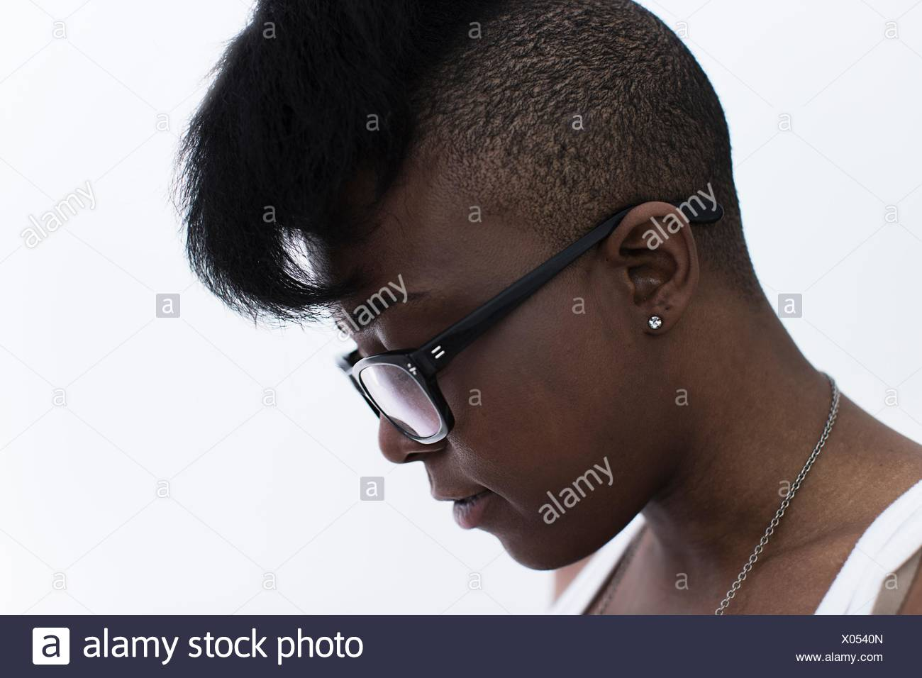 Studio profile portrait of young woman with shaved head and quiff - Stock Image
