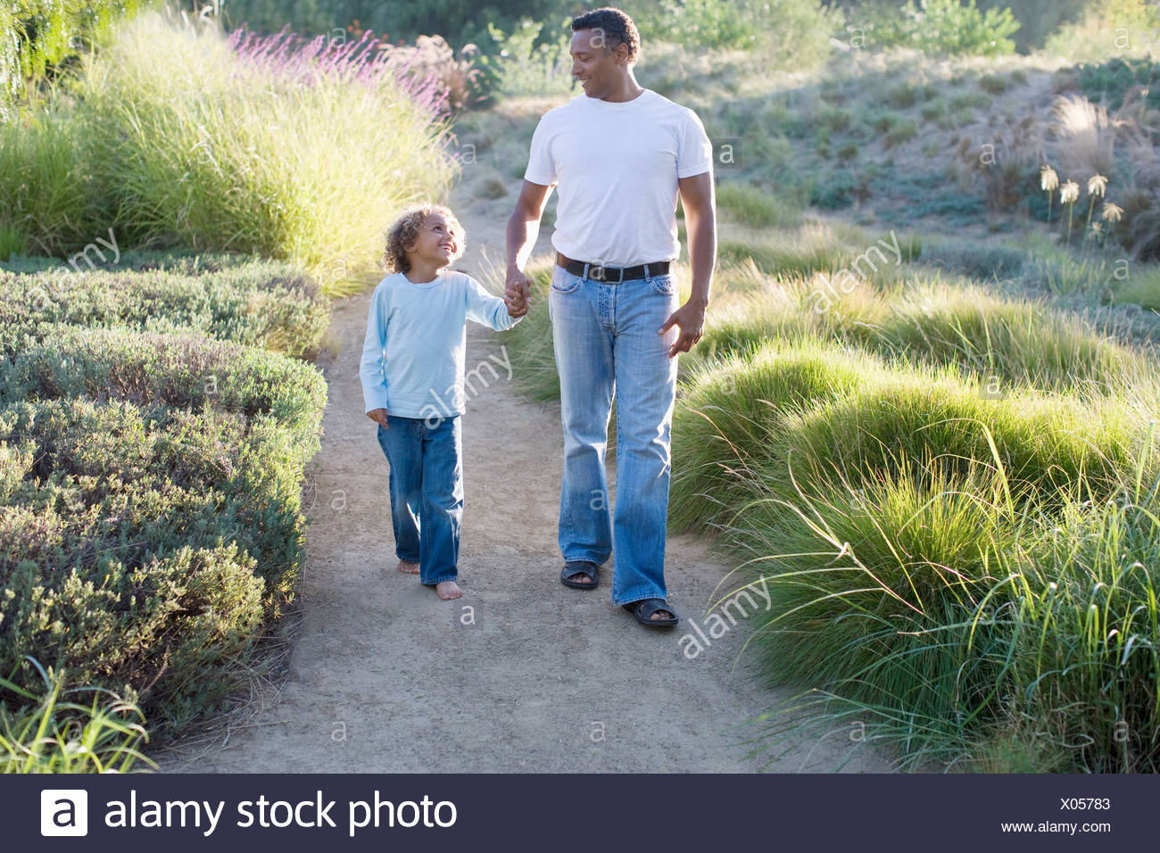 African father and son walking in garden - Stock Image