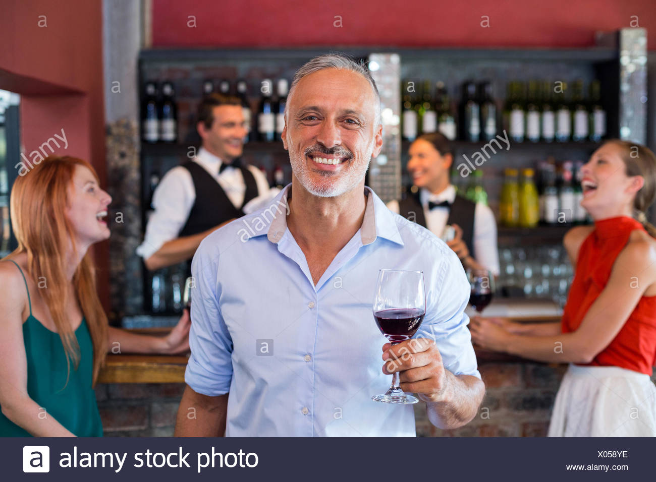 Portrait of man holding a wine glass in front of bar counter - Stock Image