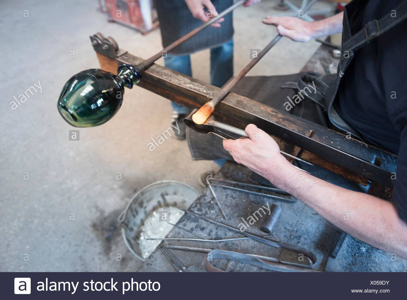 Glassblower forming hot glass - Stock Image