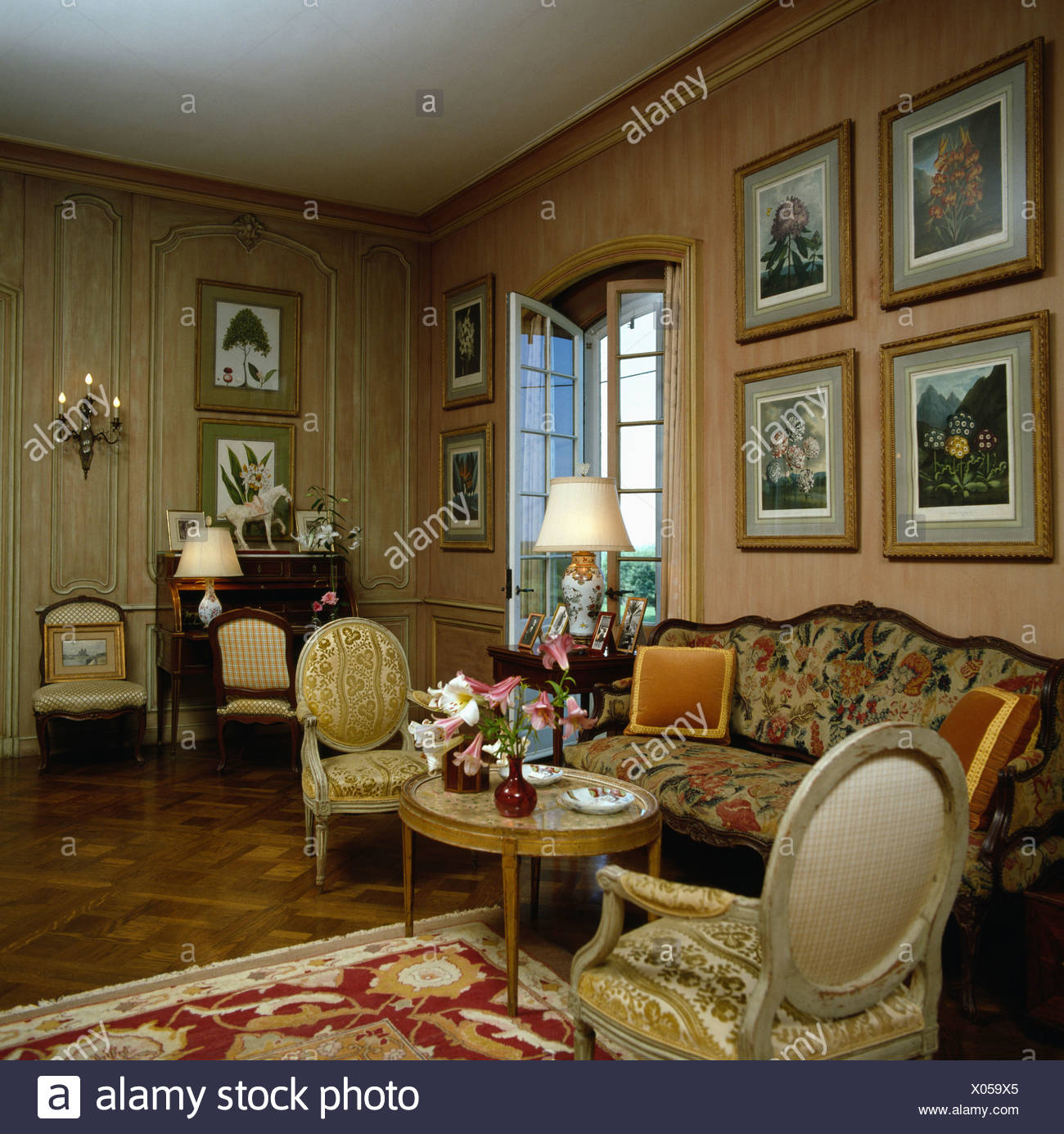 Pictures On Wall Above Patterned Sofa In Drawing Room With French Antique Furniture And Neutral Wallpaper Stock Photo Alamy