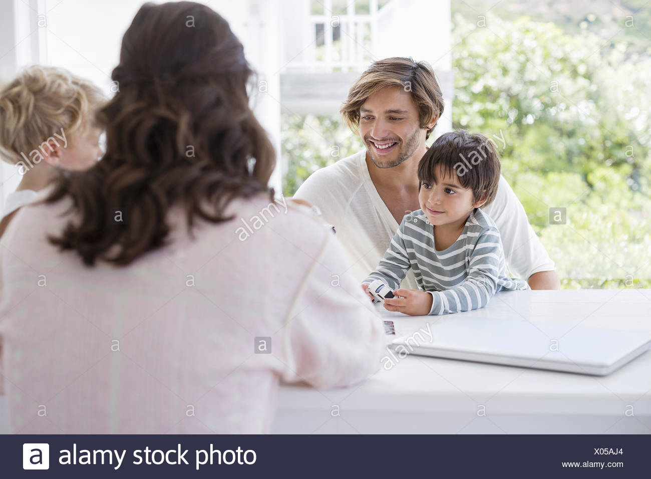 Happy young family playing at home - Stock Image