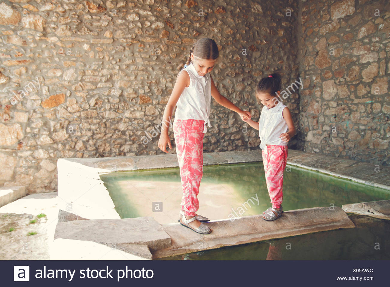 Two girls walking along ledge by a pool of water - Stock Image