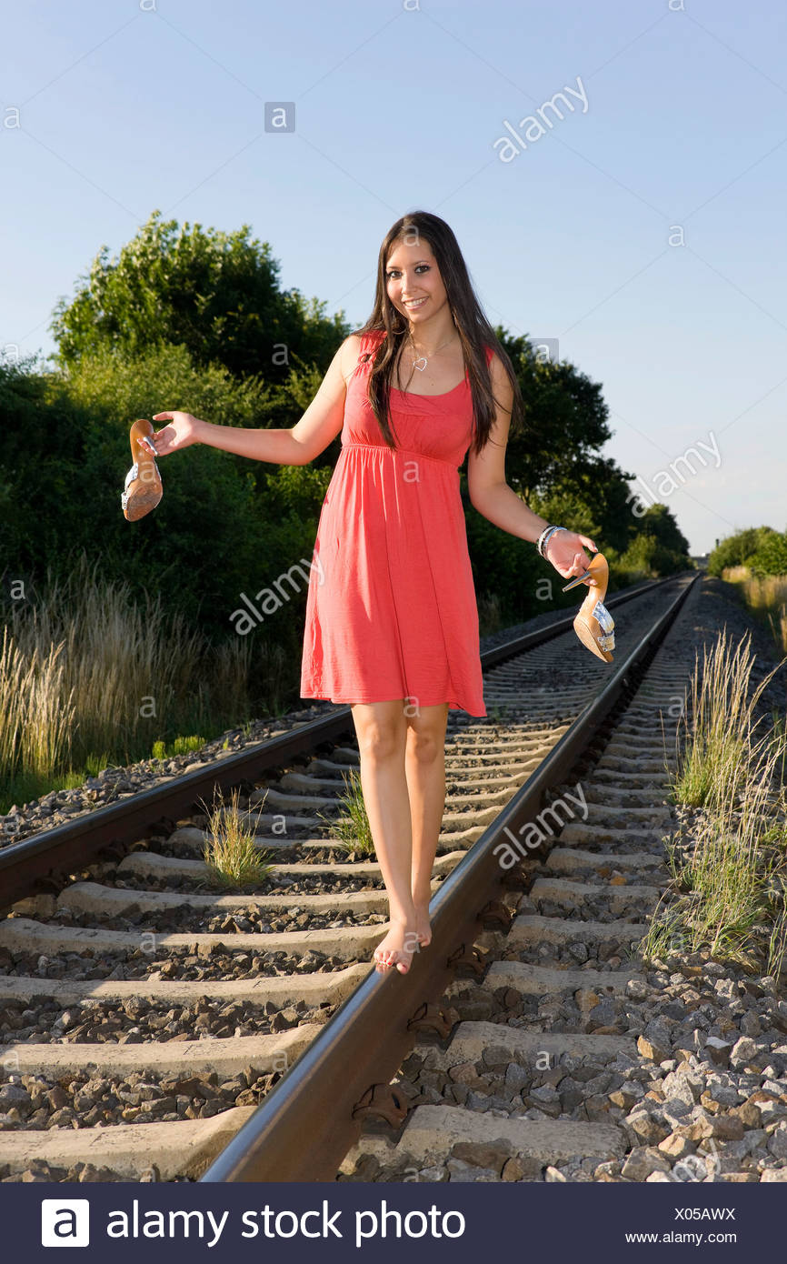 Young woman, nineteen years old, balancing barefoot on a rail - Stock Image