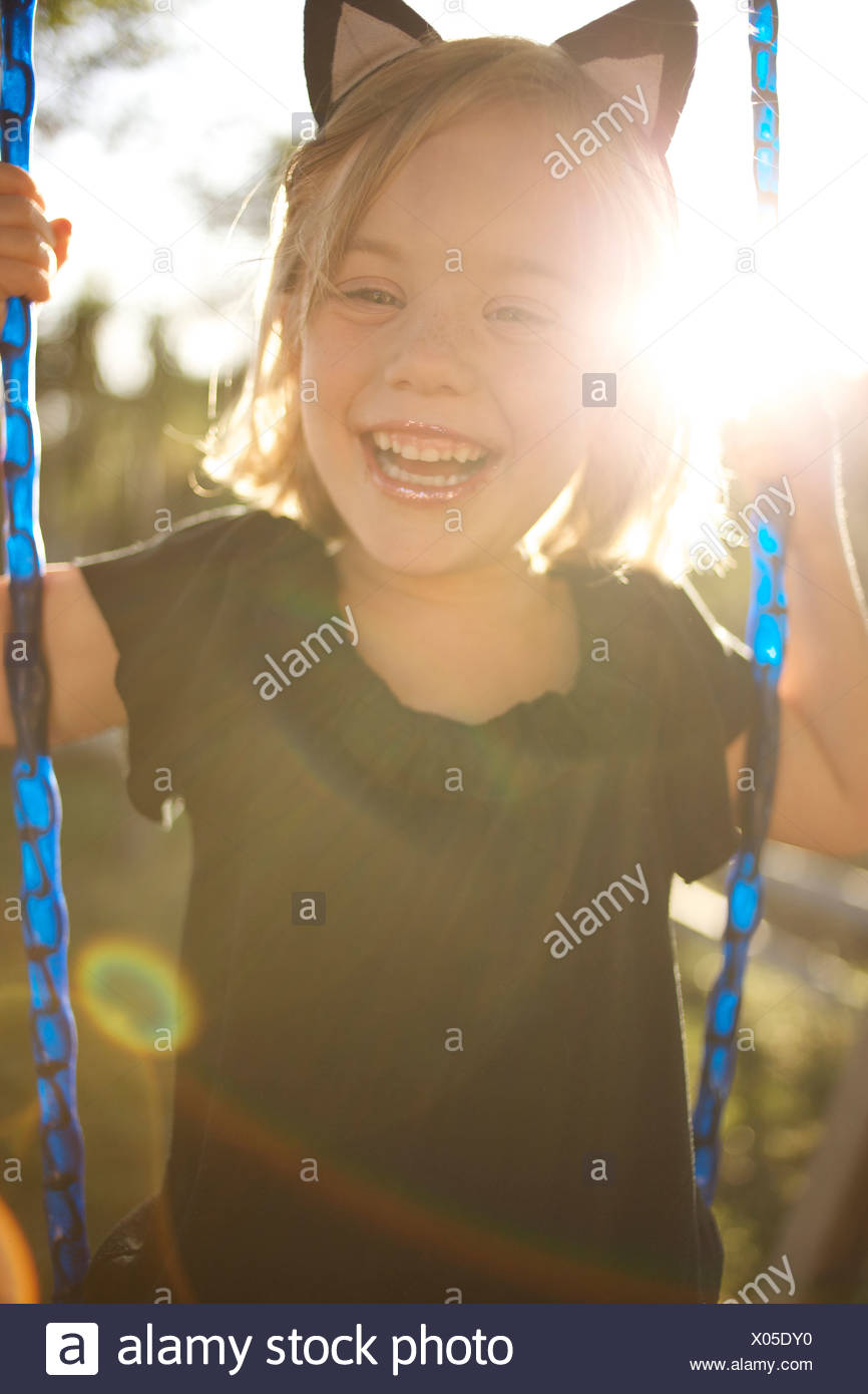Girl wearing cat ears laughs as she swings. - Stock Image