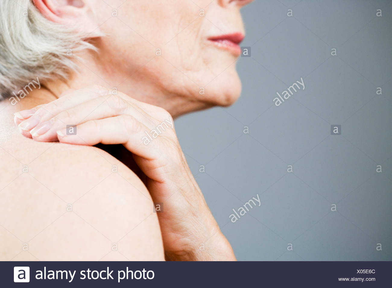 A senior woman with her hand on her shoulder - Stock Image