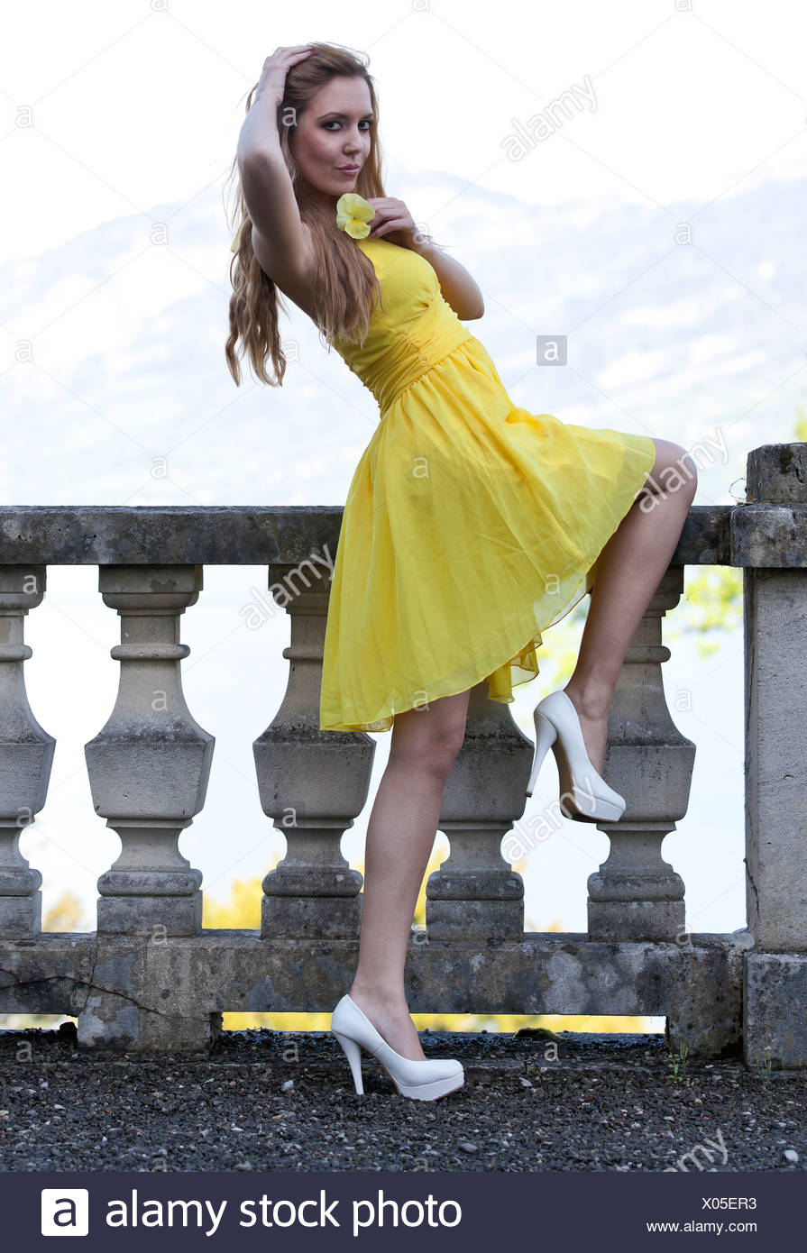 Young woman posing in a yellow dress with white high heels in front of a balustrade - Stock Image